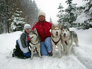 Zdjęcie przedstawia kobietę, chłopca i trzy psy rasy husky (kliknięcie spowoduje powiększenie obrazu)