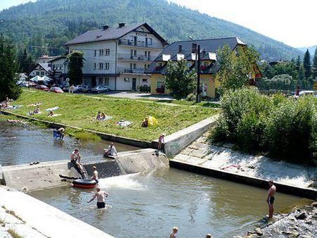 Rzeka Brennica, w tle pokoje gościnne Kaprys. (kliknięcie spowoduje powiększenie obrazu)