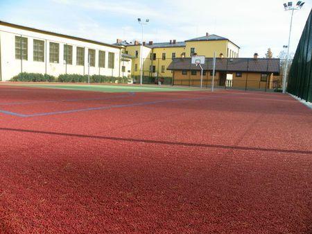 na zdjęciu boisko do koszykówki i siatkówki ze sztuczną nawierzchnią, również kosze do koszykówki, ogrodzenie odgradzające je od boiska do piłki nożnej, w tle budynek szkoły oraz sanitarno szatniowy (kliknięcie spowoduje powiększenie obrazu)