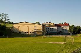 na zdjęciu bramka wkopana do ziemi i na niej zawieszona siatka, w tle zespół szkół publicznych w górkach wielkich (kliknięcie spowoduje powiększenie obrazu)